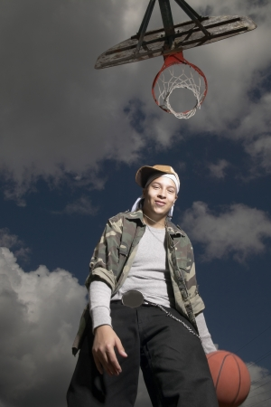 fully unbuttoned: Low angle view of a young man holding a basketball