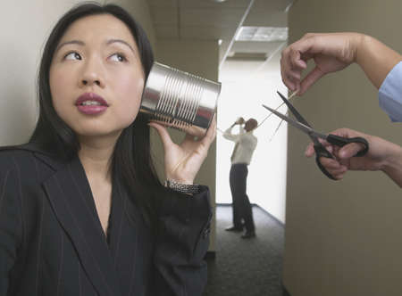 sabotage: Businesswoman talking to a man on a tin can and string phone