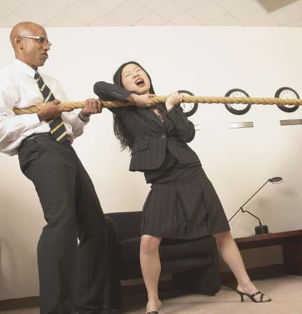 Businesswoman and a businessman pulling a rope in the office Stock Photo - 16046552