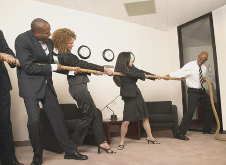 Group of business executives playing tug of war in the office Stock Photo - 16046553