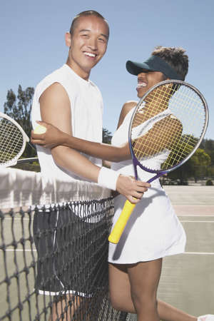 Young couple holding tennis rackets standing on a tennis court Stock Photo - 16046565