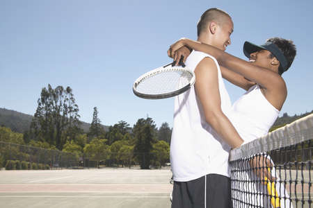 Young couple holding tennis rackets standing on a tennis court Stock Photo - 16046567