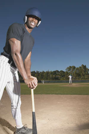 Young man standing resting on a baseball bat Stock Photo - 16046570