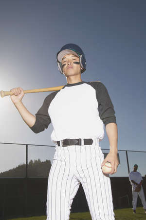 Young man standing holding a baseball bat over his shoulder Stock Photo - 16046572