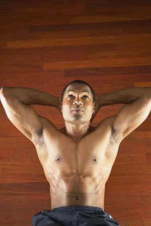 mid adult man: Hombre de mediana edad que hace ejercicios en el suelo