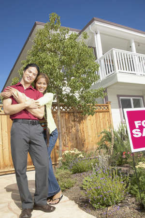 Young couple standing holding each other in front of a house for sale Stock Photo - 16046598