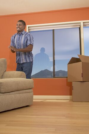 cardboard only: Young man moving furniture in a room