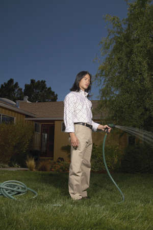 Young man watering the lawn with a hose Stock Photo - 16046648