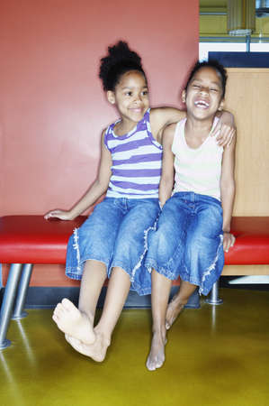 legs around: Close-up of two girls sitting on a bench