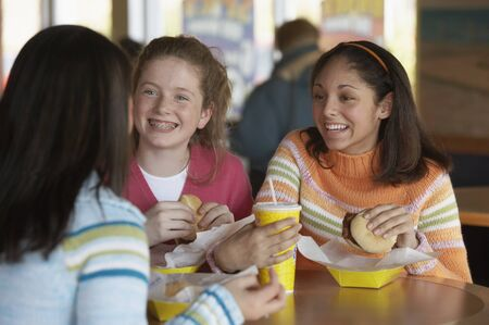 latin food: Three teenage girls sitting at a table and eating
