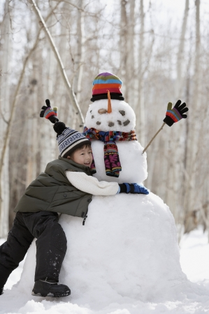 Side profile of a boy hugging a snowman