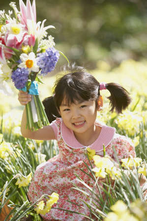 Portrait of a girl holding a bouquet of flowers in a field LANG_EVOIMAGES