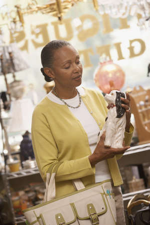 Mature woman holding a statue of a dog in a gift shop Stock Photo - 16046738
