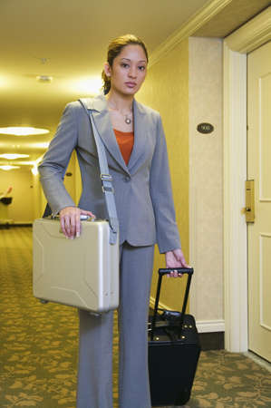 Portrait of a businesswoman holding a suitcase in a corridor Stock Photo - 16046742