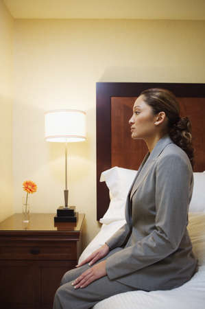 Side profile of a businesswoman sitting on a bed Stock Photo - 16046771