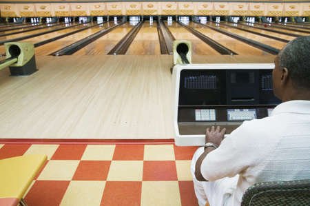 bowling alley: Rear view of a mature man sitting in a bowling alley