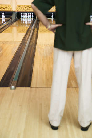 bowling alley: Rear view of a mid adult man standing in a bowling alley