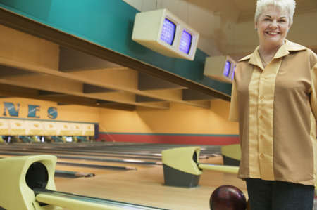 Portrait of a mature woman standing in a bowling alley Stock Photo - 16046781