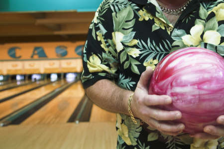 bowling alley: Mid section view of a mid adult man holding a bowling ball in a bowling alley