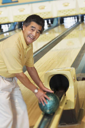 bowling alley: Portrait of a mature man taking a bowling ball from a channel in a bowling alley