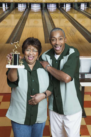 bowling alley: Portrait of a mature couple standing with a trophy in a bowling alley LANG_EVOIMAGES