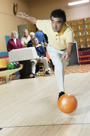 bowling alley: Mature men bowling LANG_EVOIMAGES