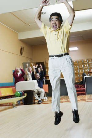 bowling alley: Mature men jumping in excitement in a bowling alley