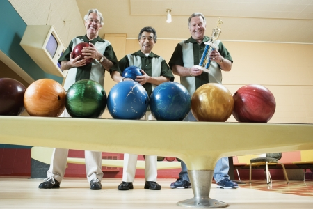 bowling ball: Portrait of three mature men holding a trophy and two bowling balls in a bowling alley LANG_EVOIMAGES