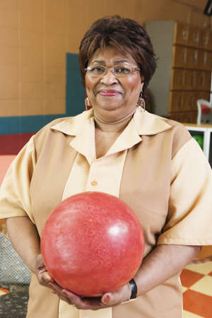 bowling alley: Portrait of a mature woman holding a bowling ball in a bowling alley