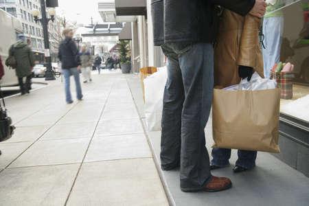 mid adult couple: Ver la secci�n baja de una pareja de mediana edad sosteniendo bolsas de la compra LANG_EVOIMAGES