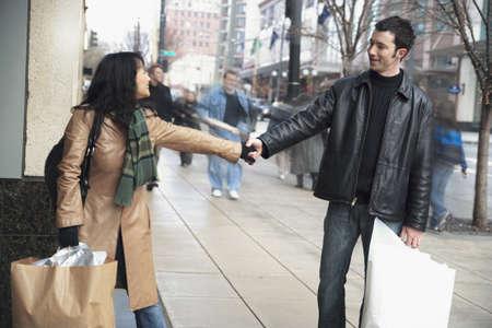mid adult couple: Pareja de mediana edad tomados de la mano y llevando bolsas de la compra