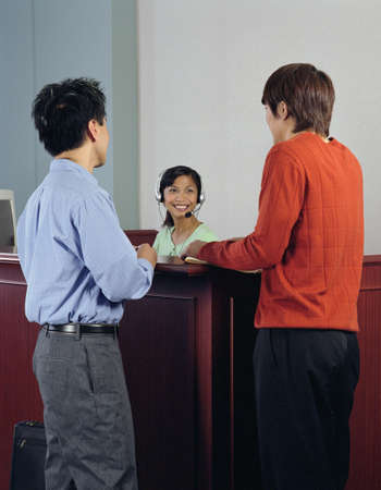 Rear view of two businessmen talking to a customer service representative Stock Photo - 16046850