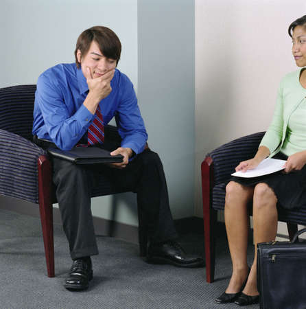 Businessman and a businesswoman sitting on arm chairs Stock Photo - 16046852