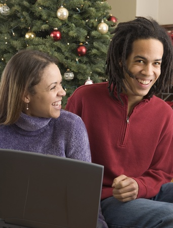 mid adult couple: Close-up of a mid adult couple smiling in front of a laptop