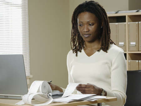 Businesswoman checking bills in an office Stock Photo - 16046889