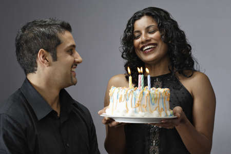 Close-up of a young woman holding a birthday cake with a young man looking at her Stock Photo - 16046891