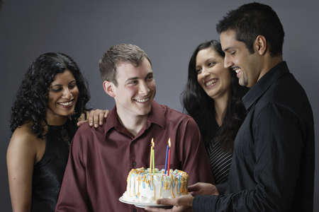 Close-up of a young man holding a birthday cake with his friends Stock Photo - 16046899