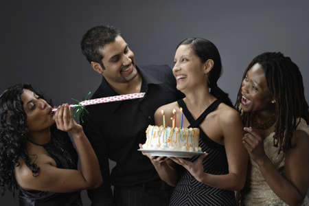 adult birthday: Young woman holding a birthday cake with her friends LANG_EVOIMAGES