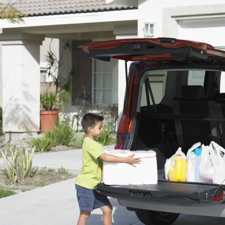 children's wear: Side profile of a boy unloading shopping bags from a car