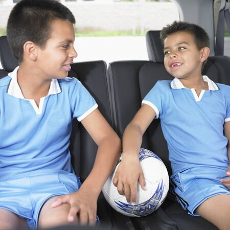Two boys sitting in the back seat of a car with a soccer ball