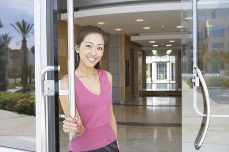 door handle: Portrait of a businesswoman standing at the entrance door of an office LANG_EVOIMAGES