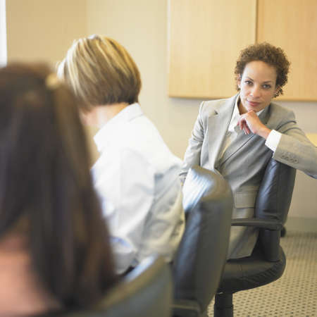 only adult: Three businesswomen discussing in a board room LANG_EVOIMAGES