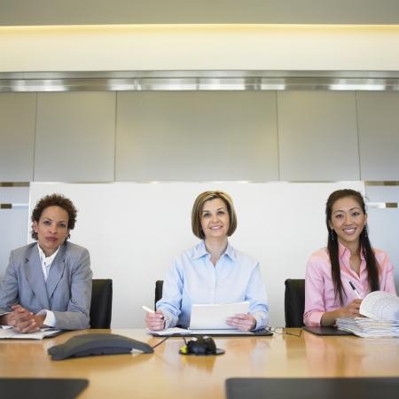 Portrait of three businesswomen sitting in a board room Imagens