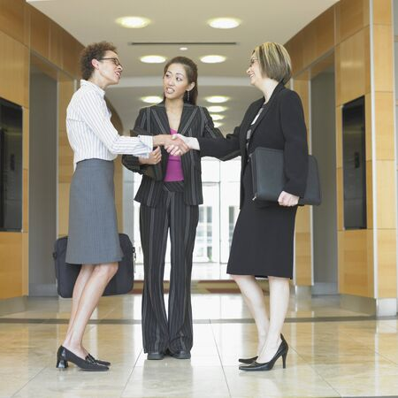 Three businesswomen standing in a corridor