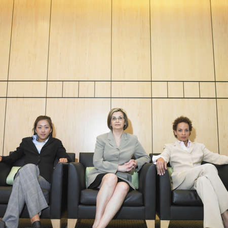legs crossed at knee: Portrait of three businesswomen sitting in an office