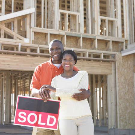 mid adult couple: Retrato de una pareja de adultos a mediados de pie delante de un signo vendidos