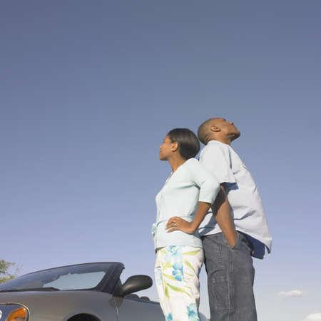 mid adult couple: �ngulo de visi�n de bajo de una pareja de adultos a mediados de pie espalda con espalda