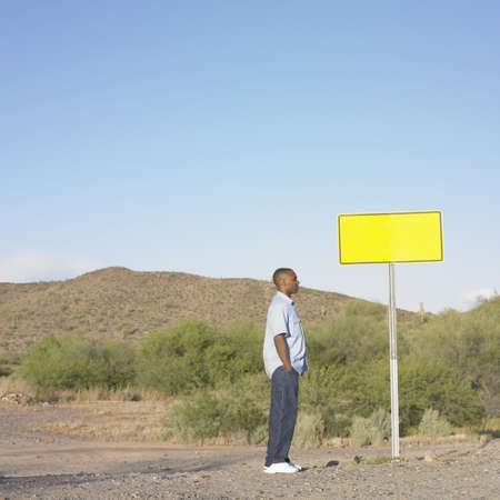 Side profile of a mid adult man standing beside a sign board Stock Photo - 16047005