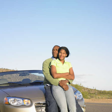 mid adult couple: Mid adult couple leaning against a convertible car LANG_EVOIMAGES