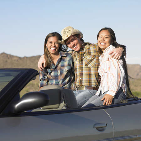 convertible car: Portrait of a young man and two young women sitting in a convertible car
